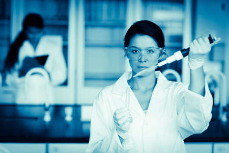 medical gloves: Scientist dropping liquid in a test tube in a laboratory