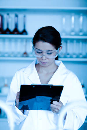taking notes: Portrait of a scientist taking notes in a laboratory