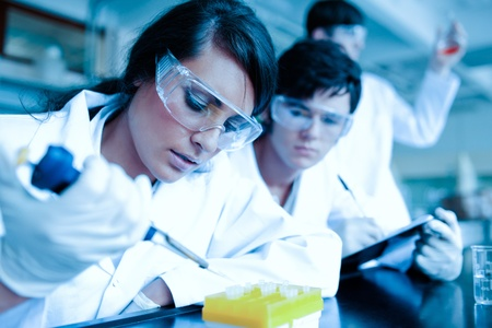 taking notes: Young scientist dropping liquid in test tubes while her partner is taking notes in a laboratory