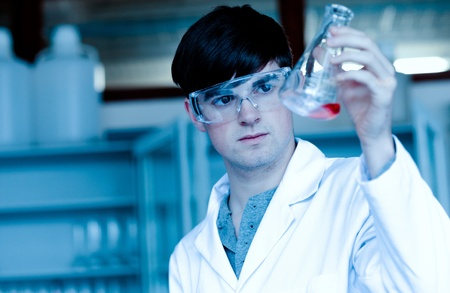 Male scientist looking at an Erlenmeyer flask in a laboratory photo