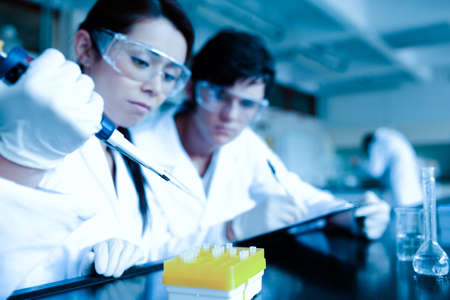 Cute scientist dropping liquid in test tubes while her partner is taking notes in a laboratory photo
