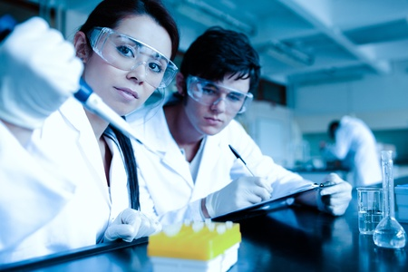 taking notes: Science student dropping liquid in test tubes while her partner is taking notes in a laboratory