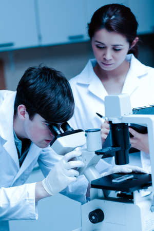 taking notes: Portrait of a young scientist looking in a microscope while another is taking notes in a laboratory