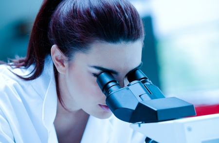see a doctor: Young scientist using a microscope in a laboratory Stock Photo