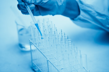 dropping: Protected hand dropping dangerous liquid in test tubes in a sterile laboratory Stock Photo