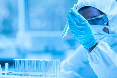 bio safety: Protected scientist looking at a dangerous liquid in test tubes in a  sterile laboratory Stock Photo