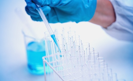 sterile: Protected hand dropping liquid in test tubes in a sterile laboratory