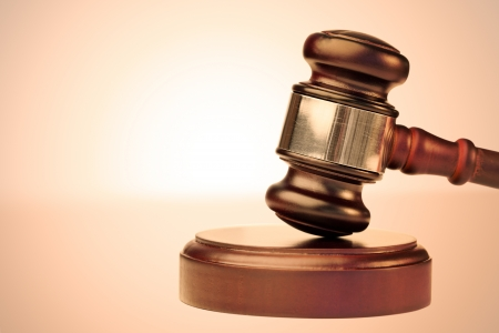 lawsuit: Close up of a brown gavel against a lighted background