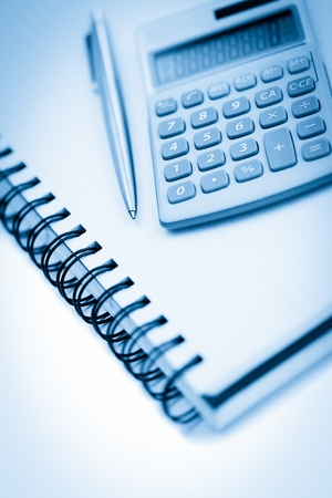 schoolroom: Angled notebook with pencil and pocket calculator on a white background