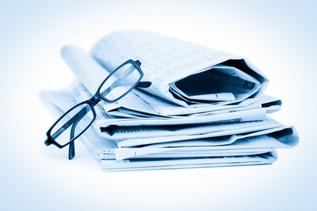 Newspapers and black glasses against a white a background photo