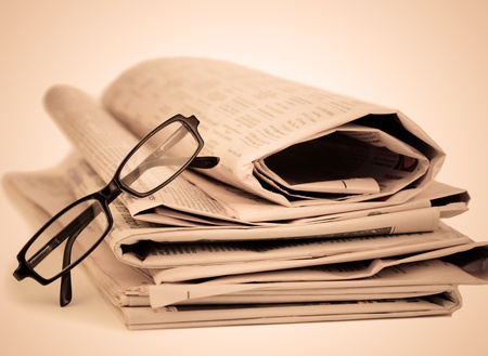 newsprint: Newspapers and black glasses against a sepia a background Stock Photo