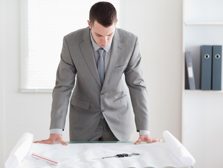 Architect standing behind a table looking at plans Stock Photo - 11619109