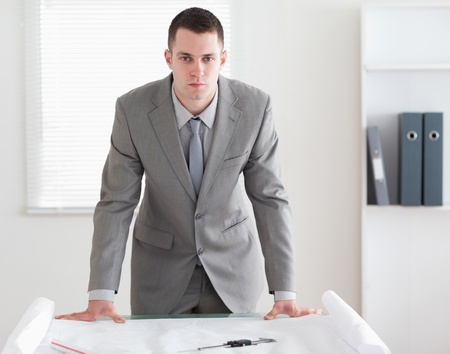 Architect standing behind a table with plans in front of him Stock Photo - 11619122
