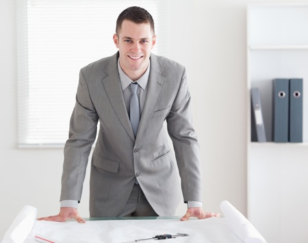 Smiling architect standing behind a table with plans in front of him Stock Photo - 11619114