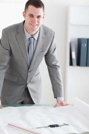 Close up of smiling architect behind a table with plans in front of him