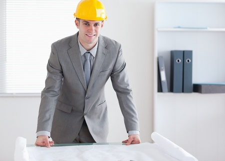 Smiling architect with helmet on standing behind a table Stock Photo - 11619249