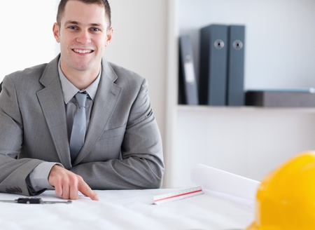 Smiling architect sitting behind a table and working on a building plan Stock Photo - 11619451