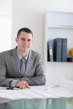 Close up of smiling architect sitting behind a table working on a plan Stock Photo - 11620370