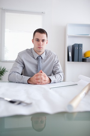 Close up of architect sitting behind a table with construction plan on it Stock Photo - 11619994