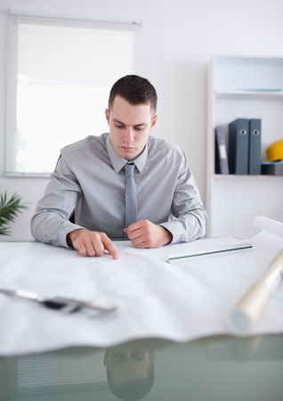 architect office: Close up of architect sitting behind a table and working on a construction plan