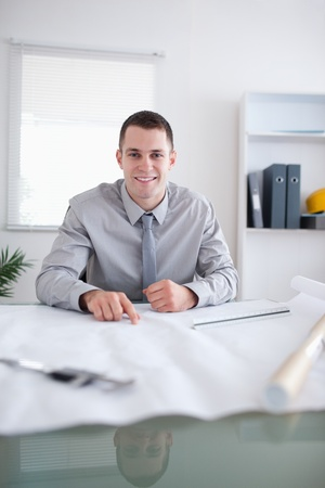Close up of smiling architect sitting behind a table working on a construction plan Stock Photo - 11619962