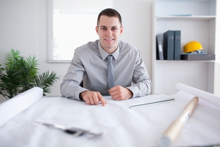 Smiling architect pointing at a plan Stock Photo - 11619956