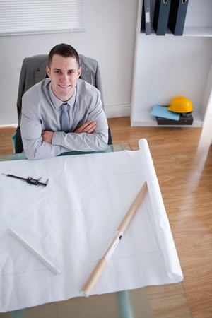 Architect with folded arms sitting behind a table photo