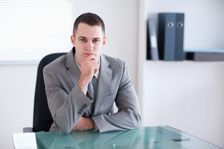 Thinking businessman sitting behind a table Stock Photo - 11620378