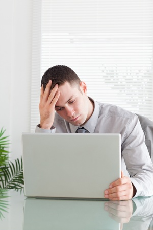 Close up of disappointed young businessman looking at his laptop  photo