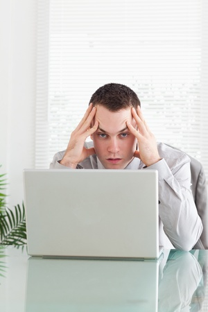 Close up of disappointed young businessman getting bad news via email Stock Photo - 11619570