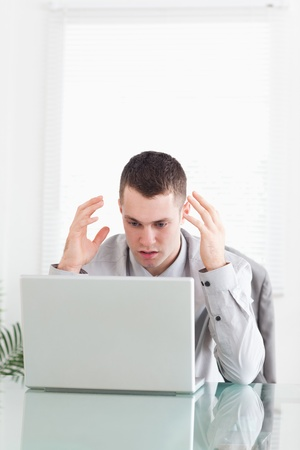 Young businessman having problems with laptop