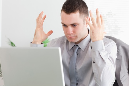 Close up of young businessman experiencing problems with his laptop Stock Photo - 11619836