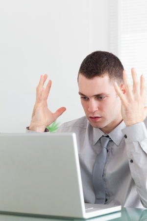 Close up of unhappy young businessman having problems with his laptop photo