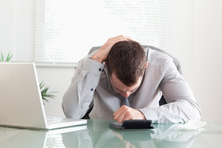 portable failure: Young businessman unhappy with his calculations Stock Photo