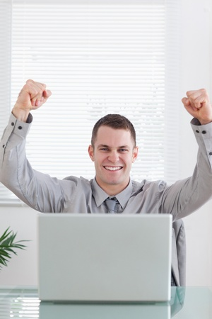 Close up of young businessman sitting behind his desk celebrating a great success Stock Photo