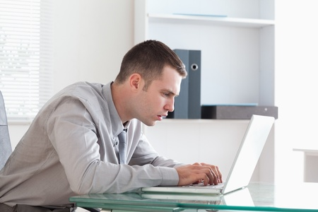 Young businessman taking close look at his laptop