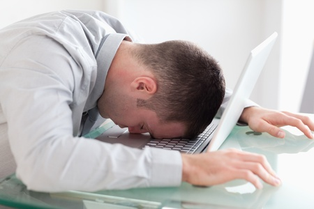 taking nap: Close up of overworked young businessman taking a nap on his laptop Stock Photo