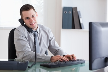 Smiling young businessman on the phone and writing on his computer photo
