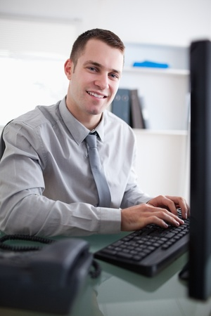 businessman working at his computer: Happy young businessman working on his computer