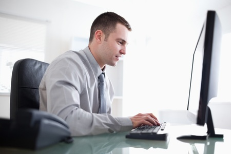 desktop computers: Young businessman working concentrated on his computer