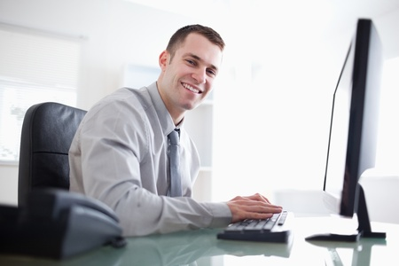 businessman working at his computer: Smiling businessman working with his computer