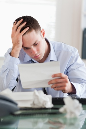 Frustrated businessman reading a bill photo