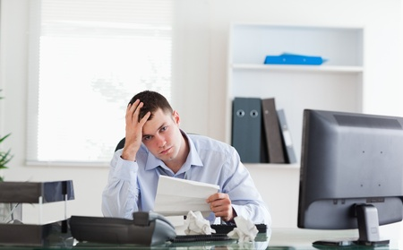 Young businessman worried about invoice photo