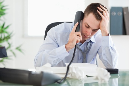 Frustrated businessman looking at an invoice while on the phone photo