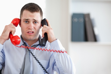 cope: Close up of stressed businessman unable to cope with the telephone Stock Photo