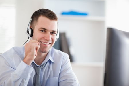 costumer: Smiling young call center agent speaking with costumer Stock Photo