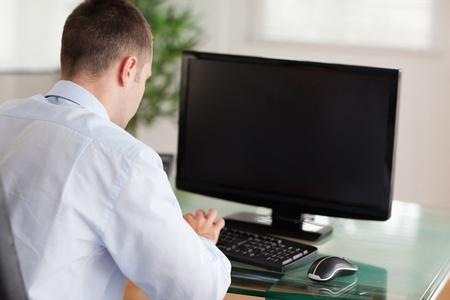 ordinateur bureau: Observation d'un jeune homme d'affaires au travail Banque d'images