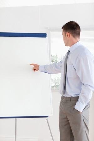 Confident businessman pointing at the middle of a flip chart photo