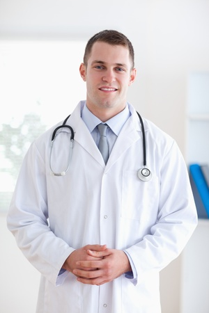 Smiling doctor with fingers folded