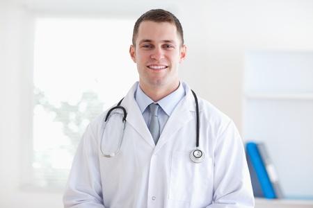 Smiling doctor standing in his practice